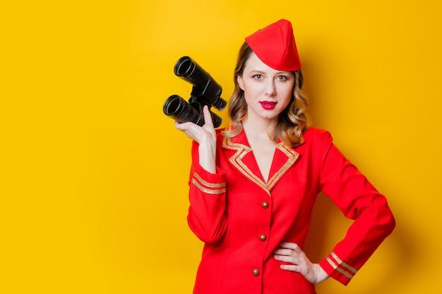Encantadora azafata vintage vestida en uniforme rojo con binoculares