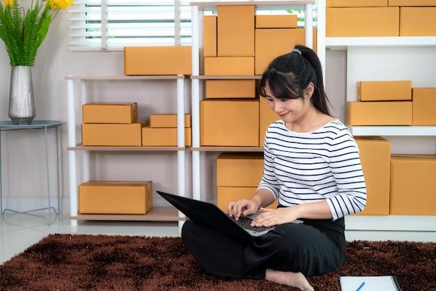 Encantadora bella asiática adolescente propietaria mujer de negocios trabajo sentado en el piso para compras en línea, buscando el pedido en la computadora portátil con equipos de oficina, concepto de estilo de vida emprendedor