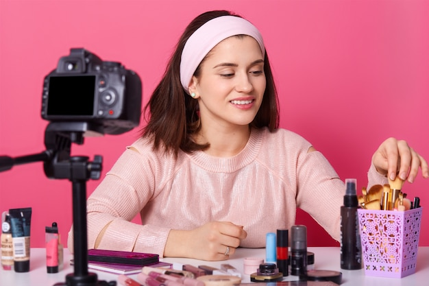 La encantadora bloguera muestra productos cosméticos mientras graba videos y da consejos para su blog de belleza, mira hacia otro lado cámara digital