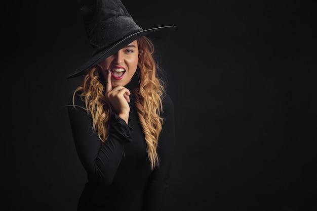 Encantadora bruja de halloween sobre pared negra