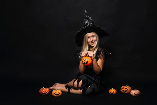 Encantadora bruja con pequeñas jack-o-linternas