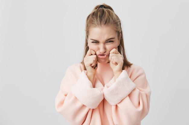 Encantadora, con el ceño fruncido, elegante chica europea con cabello rubio vestido con una sudadera rosa, pellizcando sus mejillas, burlándose, divirtiéndose y divirtiéndose. concepto de diversión, juventud y belleza.