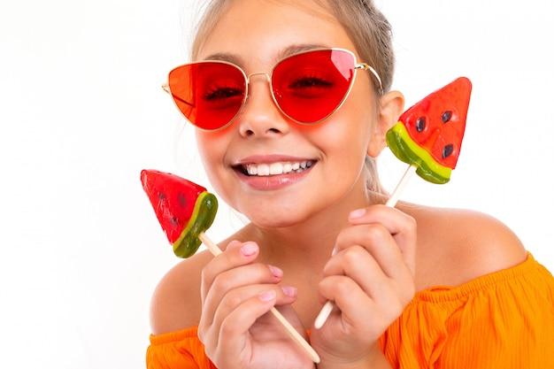 Encantadora chica adolescente con chupachups en forma de sandías de vacaciones disfruta el verano en un blanco aislado