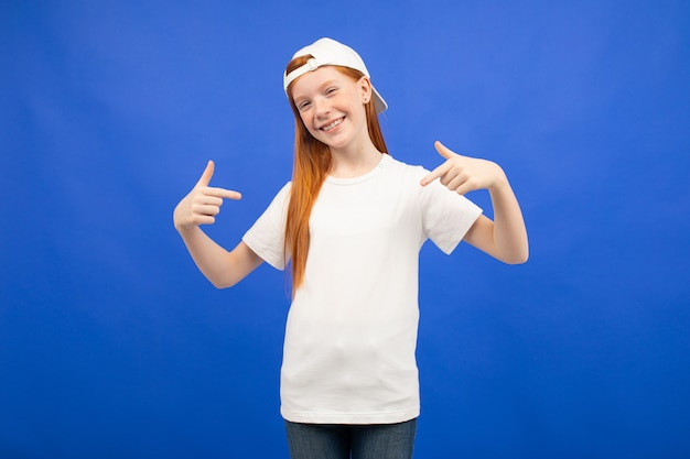 Encantadora chica adolescente pelirroja en una camiseta blanca con una maqueta estampada azul