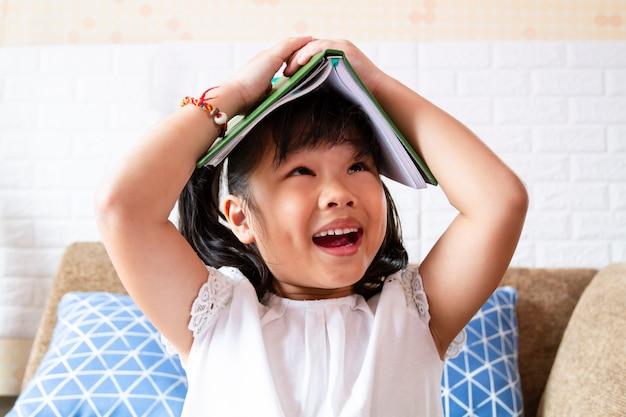 Encantadora chica alegre con un libro en la cabeza
