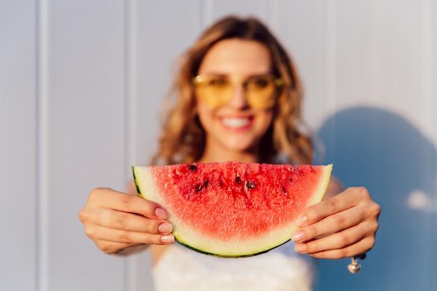 Encantadora chica alegre sosteniendo un pedazo de jugosa sandía con semillas