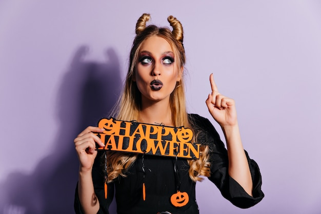 Encantadora chica blanca con maquillaje espeluznante posando con decoración de halloween. hermosa dama europea en traje de vampiro de pie en la pared púrpura.