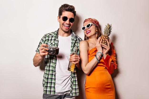 Encantadora chica con gafas de sol y elegante traje naranja y su novio posando en un espacio en blanco y sosteniendo piña, cámara retro y botella de cerveza.