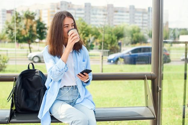 Encantadora chica hipster esperando el autobús o el tranvía en la estación de transporte público en la mañana con una taza de café