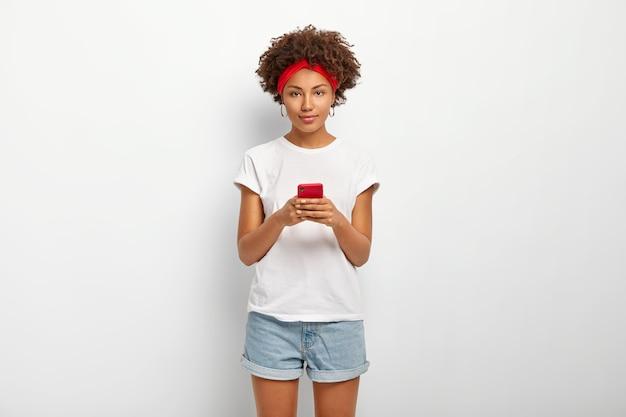 Encantadora chica hipster con peinado afro, escribe y lee comentarios, siempre en contacto.