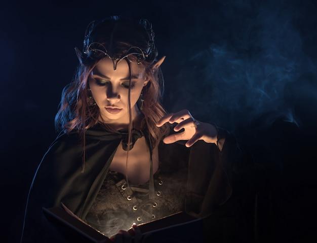 Encantadora chica en manto esmeralda practicando habilidad mágica.