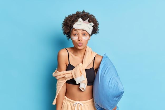 La encantadora chica milenaria afroamericana mantiene los labios redondeados mientras quiere besarte dice buenas noches desea dulces sueños vestida con un pijama aislado sobre una pared azul