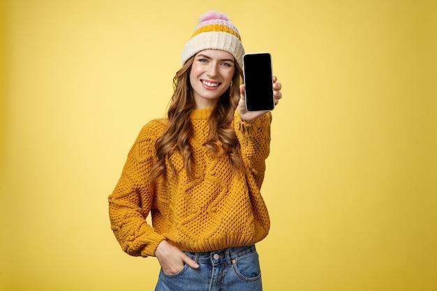 Encantadora chica de moda sonriente saliente extiende el brazo mostrando tu nuevo teléfono inteligente, muestra sonriendo satisfecho a un amigo consultor qué filtro puso usando la aplicación editar foto teléfono móvil, fondo amarillo