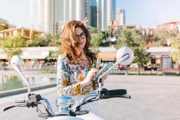 Encantadora chica morena posando juguetonamente con el teléfono en las manos de pie en la plaza con rascacielos