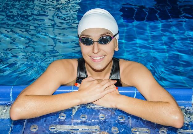 Encantadora chica nada al lado de la piscina mira a la cámara y sonríe