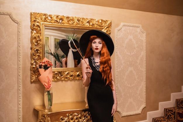 Encantadora chica pelirroja en vestido retro cerca de espejo. mujer vintage de lujo. dama con sombrero retro. mujer pelirroja en restaurante. mujer delgada con el pelo rojo. modelo encantador con boquilla. reflejo del espejo