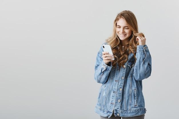 Encantadora chica rubia coqueta sonriendo al smartphone intrigado