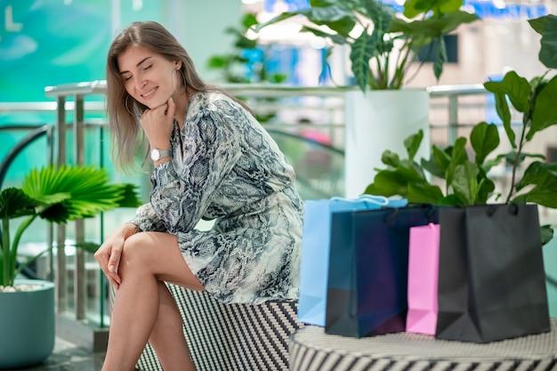 Encantadora chica rubia posando mientras estaba sentada en un banco con bolsas de compras, con los ojos cerrados, apoyando la barbilla en la mano. emoción de felicidad. viernes negro dia de descuentos.
