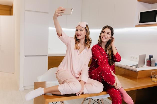Encantadora chica rubia sentada en la mesa y tomando una foto de sí misma. modelos femeninos alegres que se divierten en la cocina por la mañana.