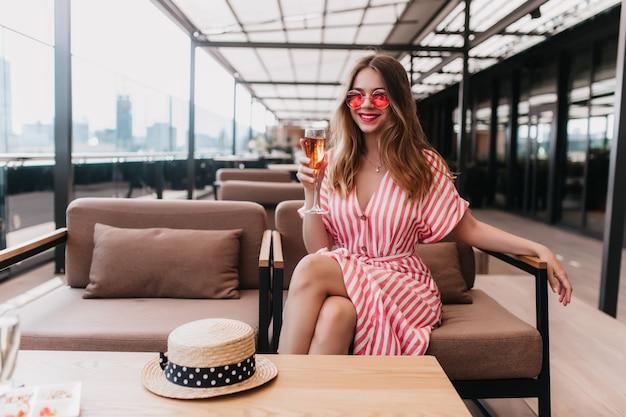 Encantadora chica rubia en vestido de rayas escalofriante en el café. sonriente a hermosa mujer joven sentada en el restaurante con una copa de vino.