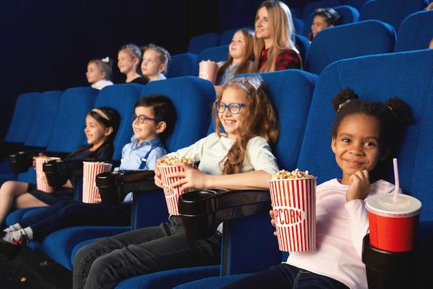 Encantadora chica sentada en el cine con amigos, mirando a cámara y sonriendo mientras ve una película. adorable niña africana comiendo palomitas de maíz y bebiendo agua dulce