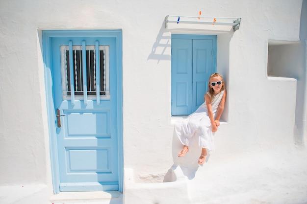 Encantadora chica en vestido blanco al aire libre en las viejas calles de mykonos. cabrito en la calle del típico pueblo tradicional griego con paredes blancas y coloridas puertas en la isla de mykonos, en grecia