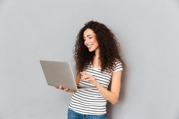 Encantadora dama con cabello rizado, correo electrónico con su amiga usando una computadora portátil plateada aislada sobre una pared gris