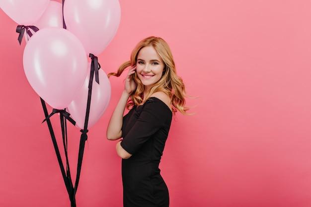 Encantadora dama delgada jugando con su cabello rubio mientras está de pie cerca de globos. foto interior de encantadora niña feliz cumpleaños relajante durante la fiesta.