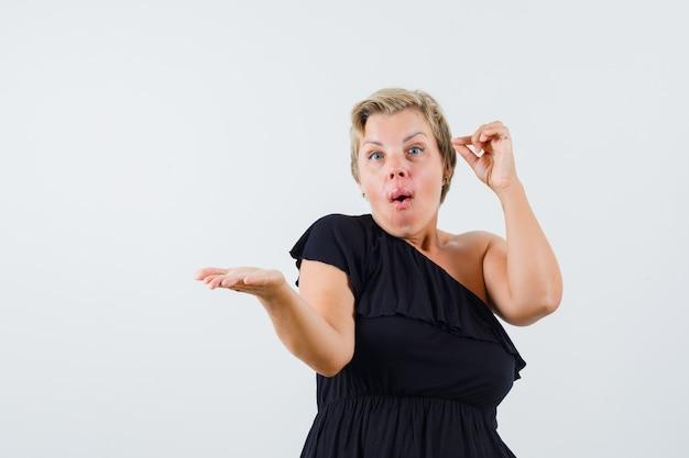 Encantadora dama extendiendo su mano mientras expresa sentimientos en la vista frontal de la blusa negra.