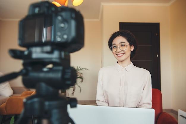 Encantadora dama morena está teniendo una reunión en línea usando una cámara