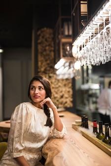 Encantadora dama sentada en barra de bar