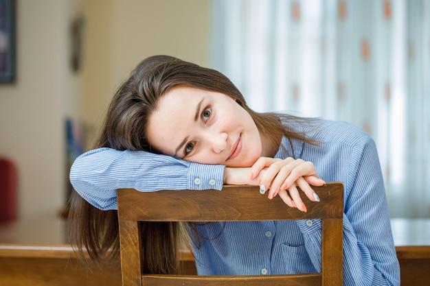 Encantadora dama sentada y sonriente en camisa azul en la habitación