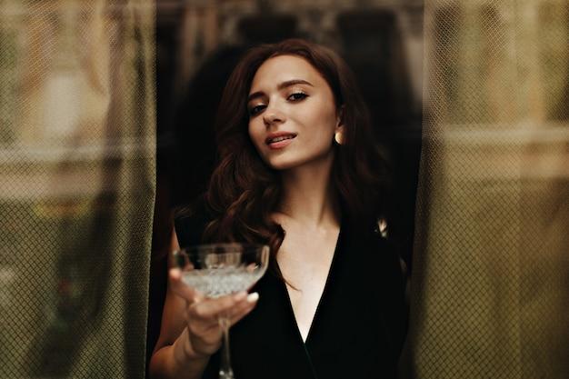 Encantadora dama en traje de terciopelo sostiene copa de martini