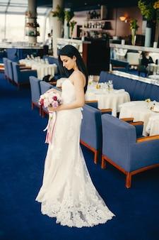 La encantadora y delgada novia morena joven viste un maravilloso vestido de novia blanco, mira atentamente el ramo, retrocede