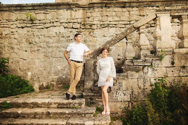 Encantadora y elegante pareja de enamorados en las escaleras del antiguo castillo vintage