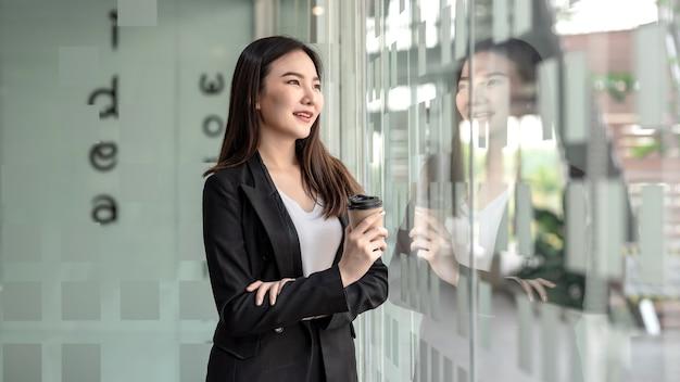 Encantadora empresaria asiática de pie sosteniendo la taza de café en la oficina.