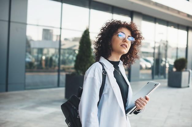 Encantadora empresaria caucásica con cabello rizado y anteojos esperando a alguien mientras sostiene una computadora portátil y usa una bolsa