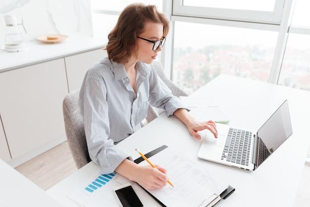 Encantadora empresaria caucásica en camisa a rayas trabajando con ordenador portátil y documentos en apartamento ligero