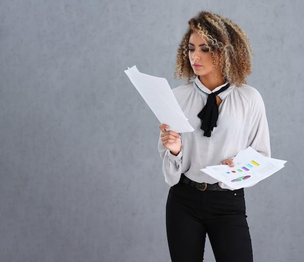 Encantadora empresaria en elegante blusa leyendo informe de estadísticas
