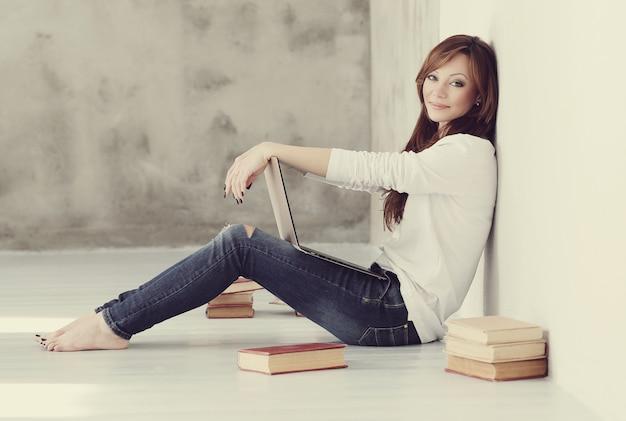 Encantadora y encantadora mujer adulta con laptop y libros
