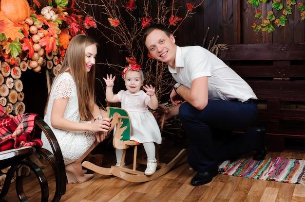 Encantadora familia sonriendo y riendo, posando a la cámara