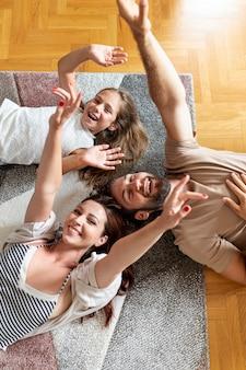 Encantadora familia tendida en el piso