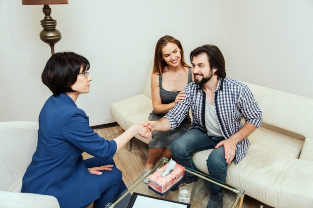 Encantadora y feliz pareja casada está sentados juntos. guy está mirando al doctor y estrechándole la mano. la mujer joven está mirando a su marido y está sosteniendo su mano en su antebrazo.