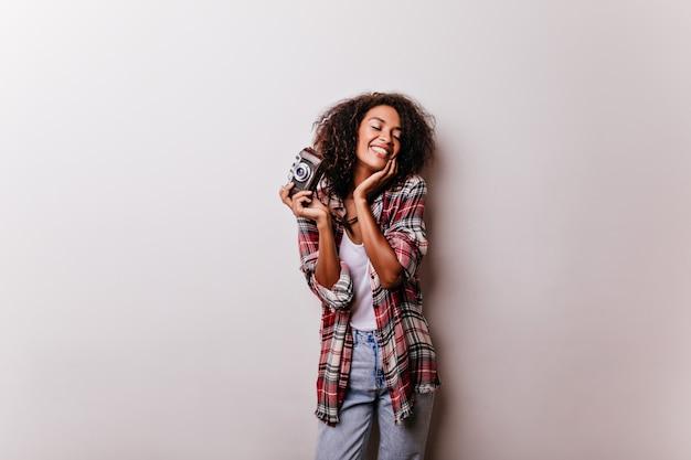 Encantadora fotógrafa feliz posando. linda dama africana con cámara de pie sobre blanco y riendo.
