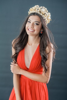 Encantadora ganadora del concurso miss, con un vestido rojo y una corona.