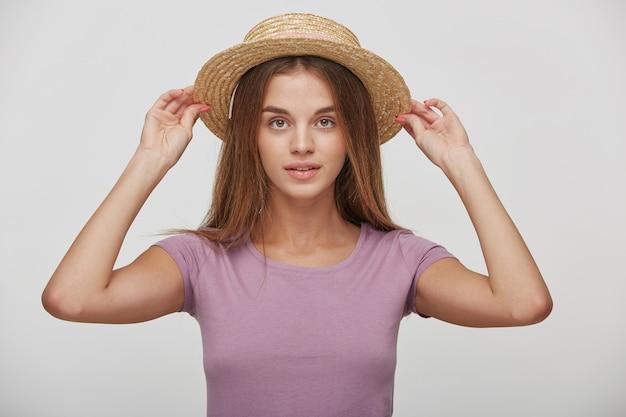 Encantadora hembra joven mantiene en manos sombrero de paja, se lo prueba o corrige