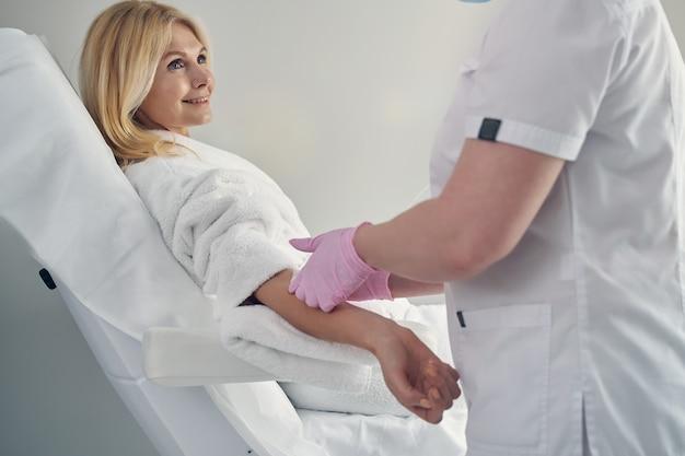 Encantadora hembra madura recibiendo terapia con vitaminas con la ayuda de una canulación intravenosa