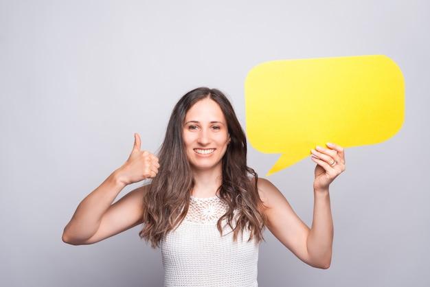 Encantadora hermosa joven mostrando el pulgar hacia arriba gesto y sosteniendo el bocadillo de diálogo en blanco vacío