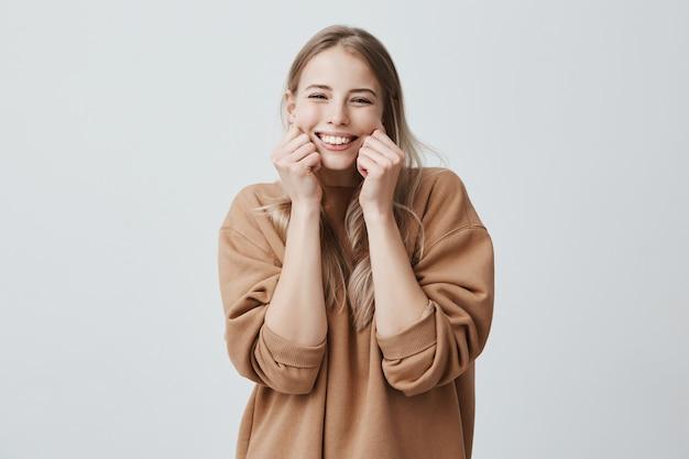Encantadora hermosa modelo femenina sonriendo ampliamente con un suéter marrón, pellizcando sus mejillas, burlándose, divirtiéndose y divirtiéndose. emociones y sentimientos positivos
