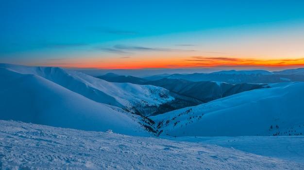 Encantadora hermosa vista de las montañas y colinas en el valle nevado en la noche.